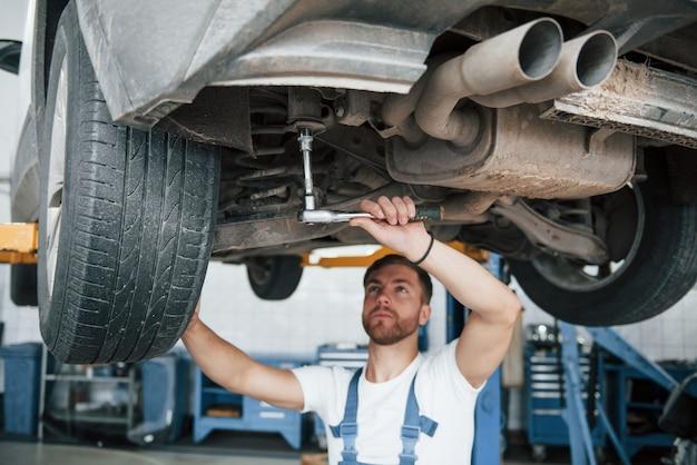 사진에 충격 흡수 장치. 파란색 유니폼을 입은 직원이 자동차 살롱에서 일합니다.