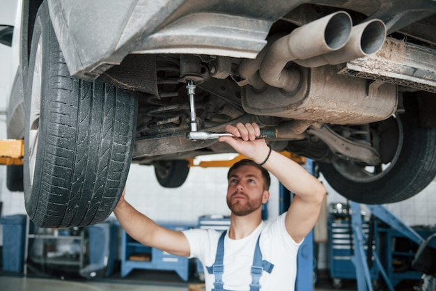 Shock absorbers on photo. employee in the blue colored uniform works in the automobile salon.