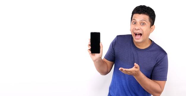 Шок и удивление лицо азиатского мужчины, представляющего смартфон на белом