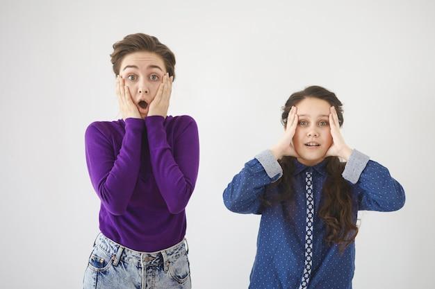 衝撃、驚き、驚きのコンセプト。感情的なバグは、若い女性と彼女の娘が口を大きく開いたまま、顔に手をつないでいることに目を向けました