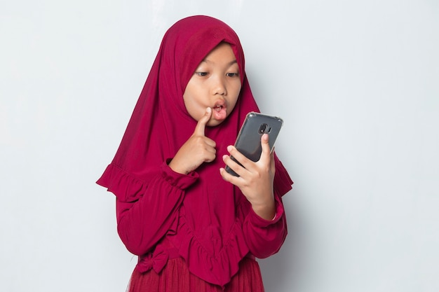 Shock muslim asian little girl using smart phone on white background