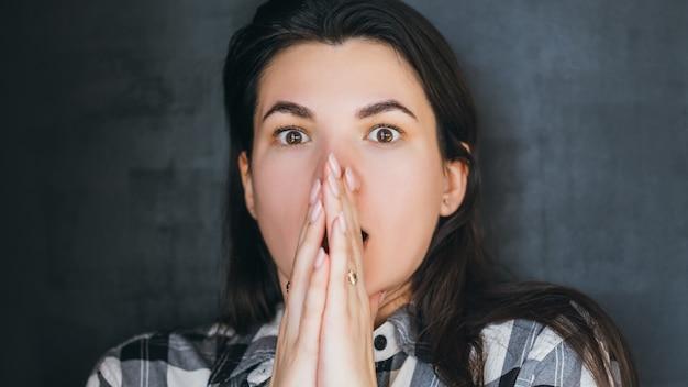 ショックパニック恐怖。怖い若い女性。恐怖の口が開いた状態で目が膨らむ。