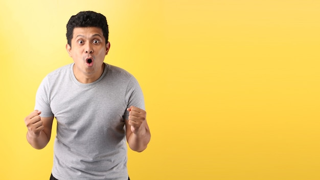 Shock and surprise face of asian man on empty space isolated on yellow background.