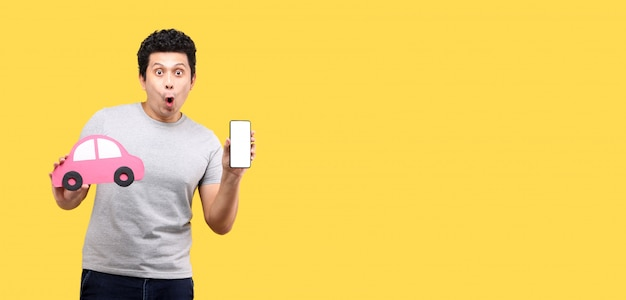 Shock and surprise face of asian man holding paper car shape presenting smart phone isolated on yellow wall