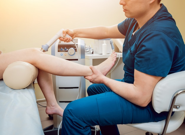 Shock wave therapy. the magnetic field, rehabilitation. physiotherapist doctor performs surgery on a patient's knee