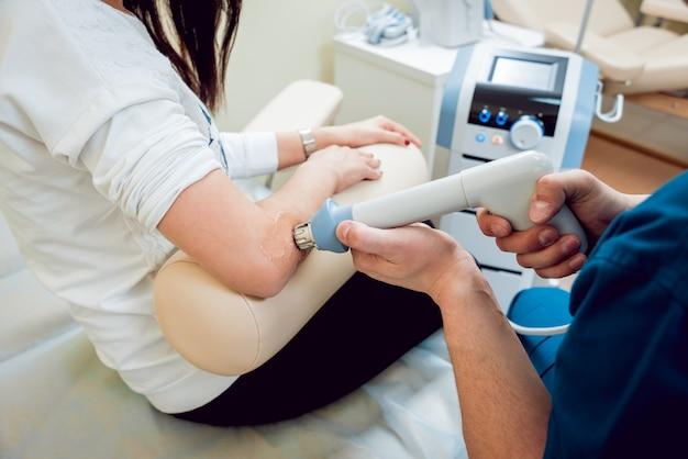 衝撃波療法。磁場、リハビリ。理学療法士の医師が患者の肘の手術を行います