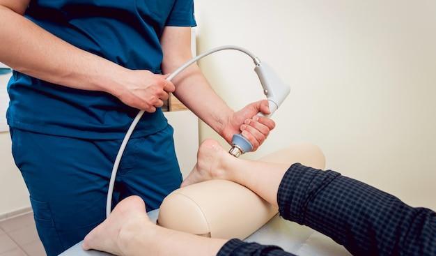 衝撃波療法。磁場、リハビリ。理学療法士の医師が患者の踵に手術を行います