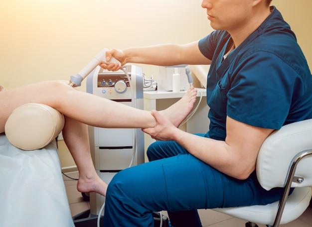 衝撃波療法。磁場、リハビリ。理学療法士の医師が患者の膝の手術を行います