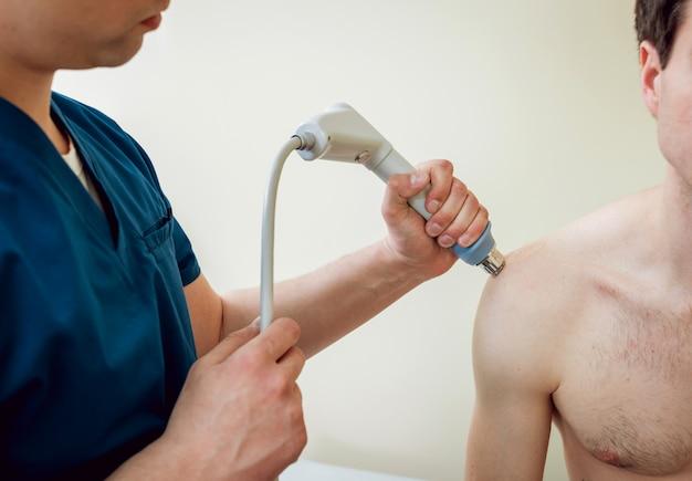 衝撃波療法。磁場、リハビリ。理学療法士の医師が患者の肩に手術を行います