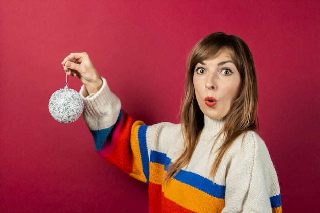 Shock young woman holding in hand a decorative silver ball on a burgundy background. concept preparation for the holidays, christmas, new year.