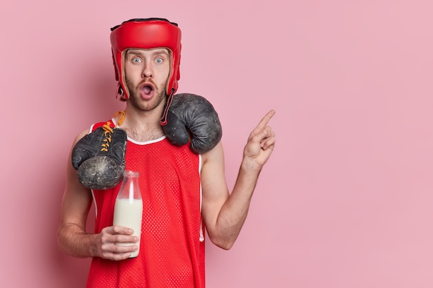 Shocked active male boxer dressed in activewear has boxing gloves around neck holds bottle of milk as source of calcium points away on copy space.