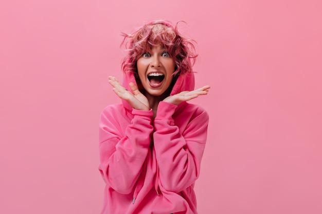 분홍색 후드티를 입은 활동적인 여성이 외진 곳에 행복하게 비명을 지른다