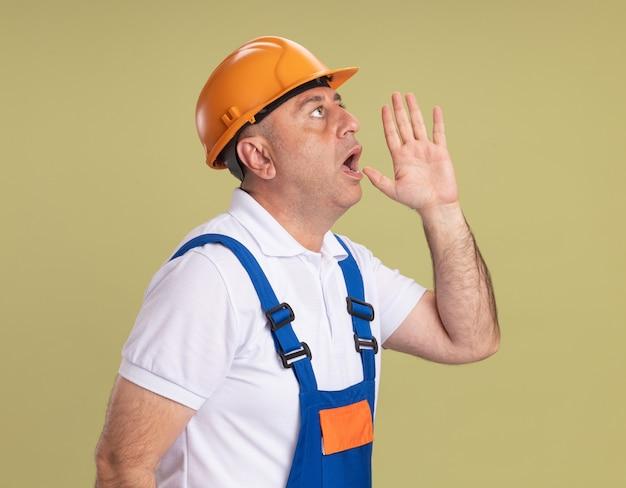 Shocked adult builder man holds hand close to mouth looking at side isolated on olive green wall