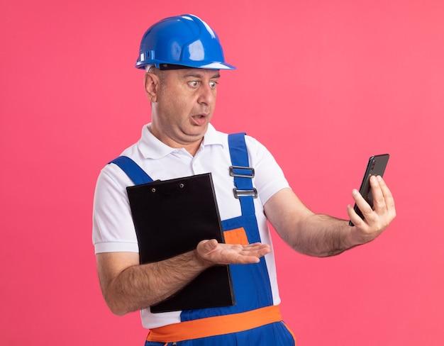 L'uomo adulto scioccato del costruttore in uniforme tiene la lavagna per appunti e guarda il telefono isolato sulla parete rosa