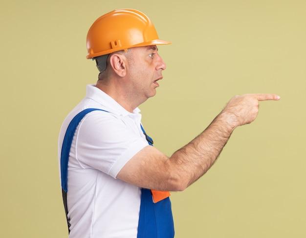 L'uomo adulto scioccato del costruttore in uniforme si leva in piedi obliquamente guardando e indicando a lato su verde oliva