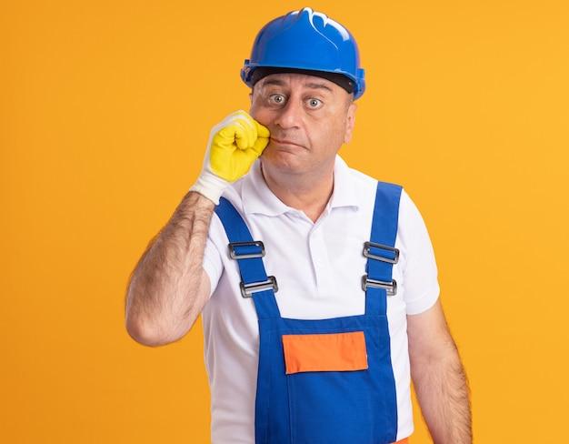 Uomo adulto scioccato del costruttore in uniforme che indossa guanti protettivi con cerniera lampo bocca isolata sulla parete arancione