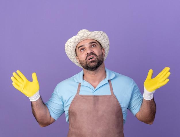 Шокированный взрослый кавказский садовник в садовой шляпе и перчатках стоит с поднятыми руками, глядя вверх