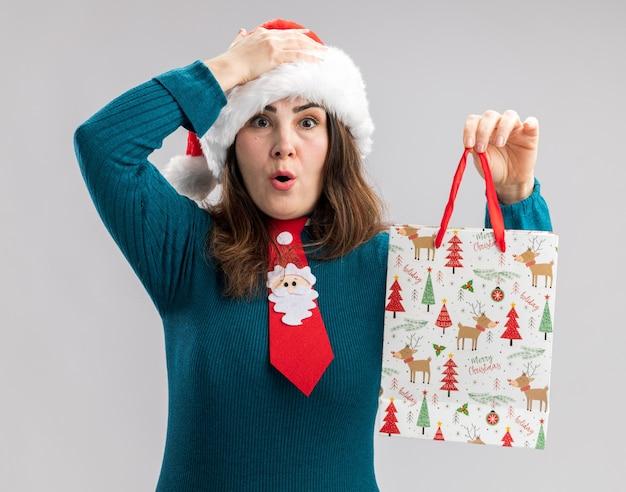 サンタの帽子とサンタのネクタイとショックを受けた大人の白人女性が頭に手を置き、コピースペースと白い背景で隔離の紙のギフトボックスを保持します。