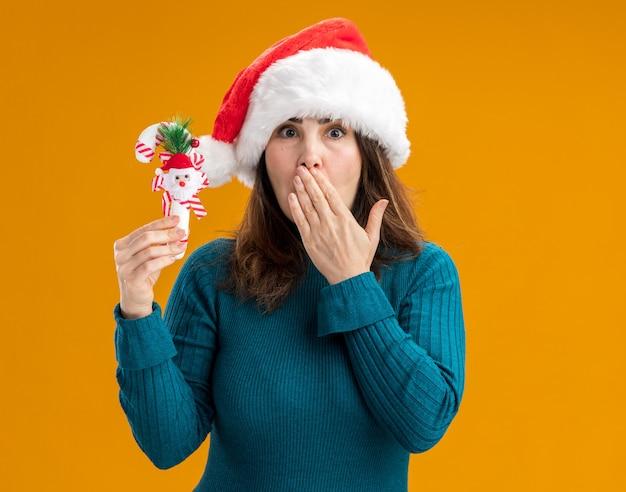 Шокированная взрослая кавказская женщина в новогодней шапке кладет руку на рот и держит конфету, изолированную на оранжевом фоне с копией пространства