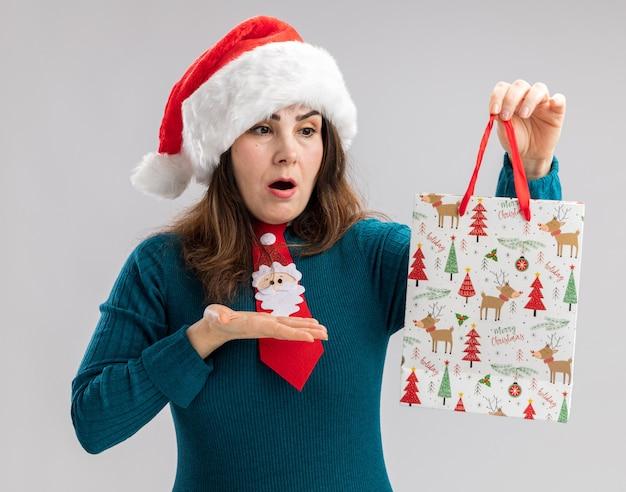 Donna caucasica adulta scioccata con cappello da babbo natale e cravatta da babbo natale che guarda e indica una scatola regalo di carta isolata sul muro bianco con spazio di copia