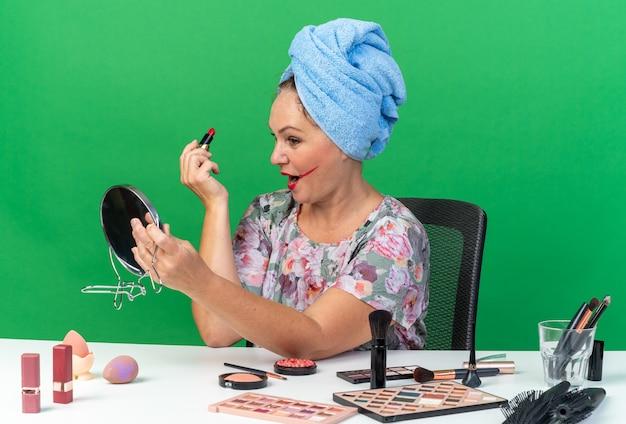 Donna caucasica adulta scioccata con i capelli avvolti in un asciugamano seduto al tavolo con strumenti per il trucco che tengono rossetto e guardando lo specchio isolato sulla parete verde con spazio di copia