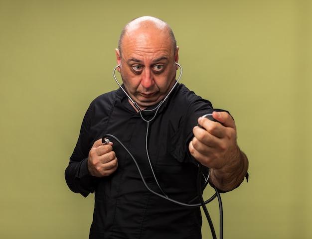 Uomo caucasico malato adulto scioccato che tiene e guarda lo sfigmomanometro isolato sulla parete verde oliva con spazio di copia