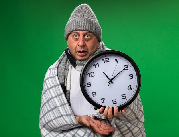 Scioccato adulto malato uomo caucasico con sciarpa intorno al collo indossando cappello invernale avvolto in plaid tenendo l'orologio isolato sulla parete verde con spazio copia
