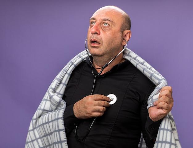Scioccato adulto malato uomo caucasico avvolto in plaid misurazione battito cardiaco con stetoscopio guardando lato isolato sul muro viola con spazio di copia