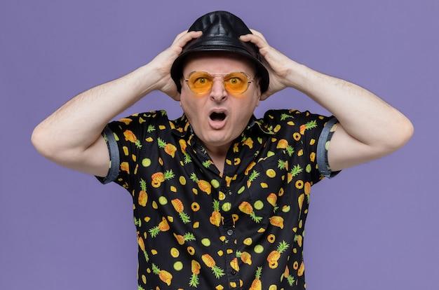 Uomo adulto scioccato con cappello a cilindro nero che indossa occhiali da sole mettendo le mani sul cappello e guardando