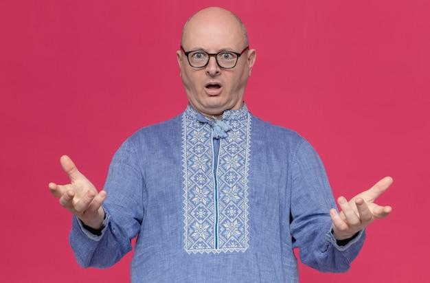 Шокирован взрослый славянский мужчина в синей рубашке в оптических очках, держа руки открытыми и