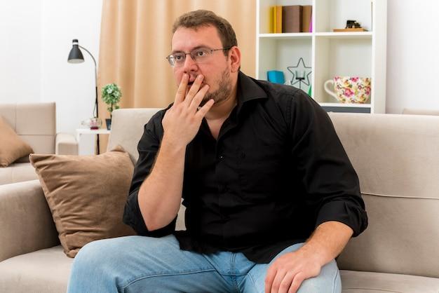 광학 안경에 충격을받은 성인 슬라브 남자가 안락 의자에 앉아 입에 손을 대고 거실 내부를보고 있습니다.