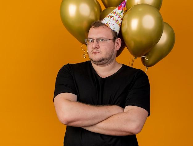 생일 모자를 쓰고 광학 안경에 충격을받은 성인 슬라브 남자는 헬륨 풍선 앞에서 교차 팔로 서 있습니다.
