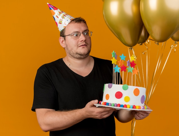 Shocked adult slavic man in optical glasses wearing birthday cap holds helium balloons and birthday cake