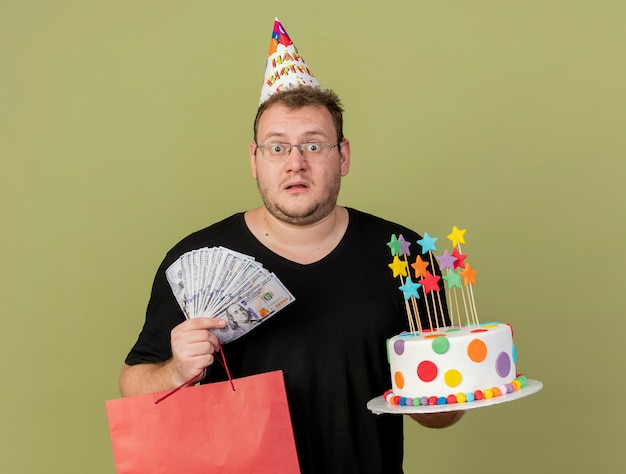 Shocked adult slavic man in optical glasses wearing birthday cap holds money paper shopping bag and birthday cake