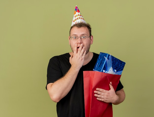 Shocked adult slavic man in optical glasses wearing birthday cap puts hand on mouth and holds gift box in paper shopping bag