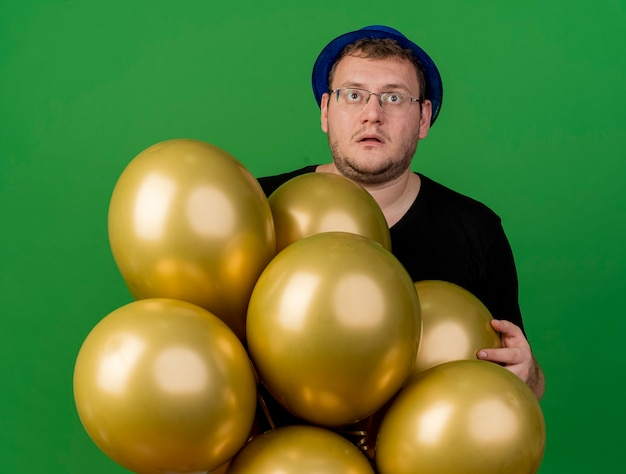 Shocked adult slavic man in optical glasses wearing blue party hat holds helium balloons looking up