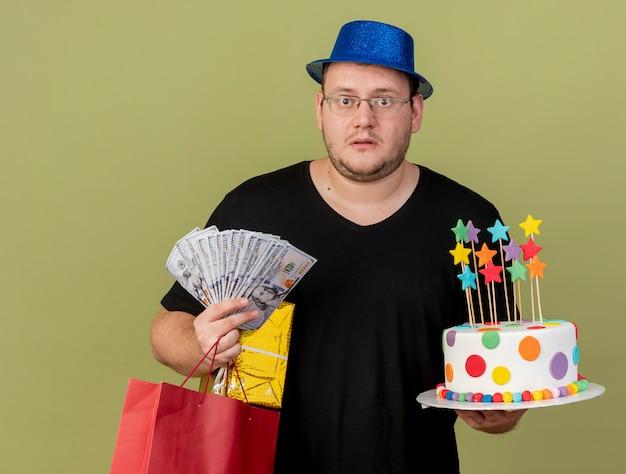 L'uomo slavo adulto scioccato in occhiali ottici che indossa un cappello da festa blu tiene in mano una scatola regalo di soldi, una borsa della spesa di carta e una torta di compleanno