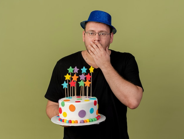 Shocked adult slavic man in optical glasses wearing blue party hat puts hand on mouth and holds birthday cake