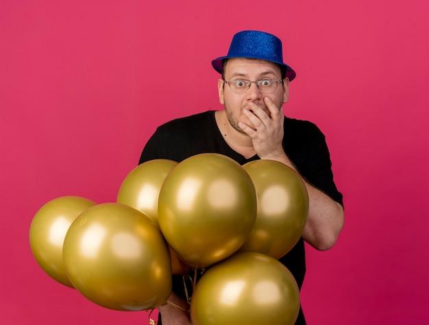 Uomo slavo adulto scioccato con occhiali ottici che indossa un cappello da festa blu mette la mano sulla bocca e tiene palloncini di elio
