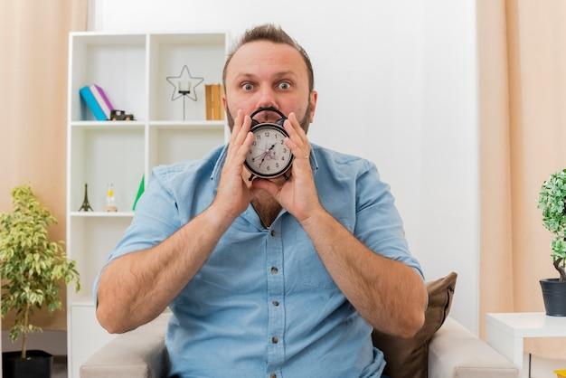 ショックを受けた大人のスラブ人は、リビングルーム内の目覚まし時計を保持している肘掛け椅子に座っています