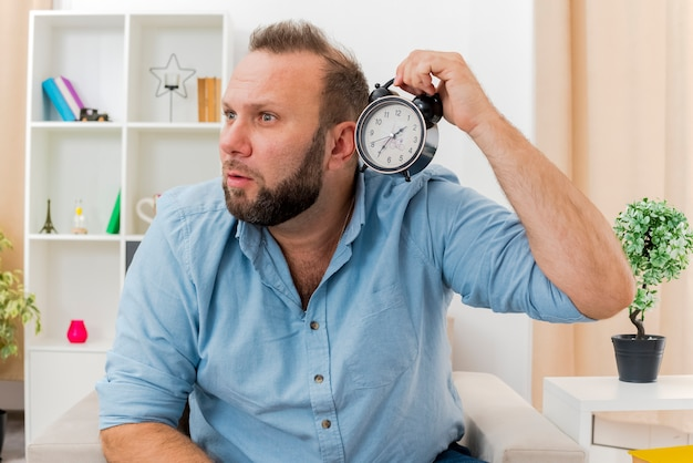 ショックを受けた大人のスラブ人は、リビングルームの内側を見ている目覚まし時計を持って肘掛け椅子に座っています