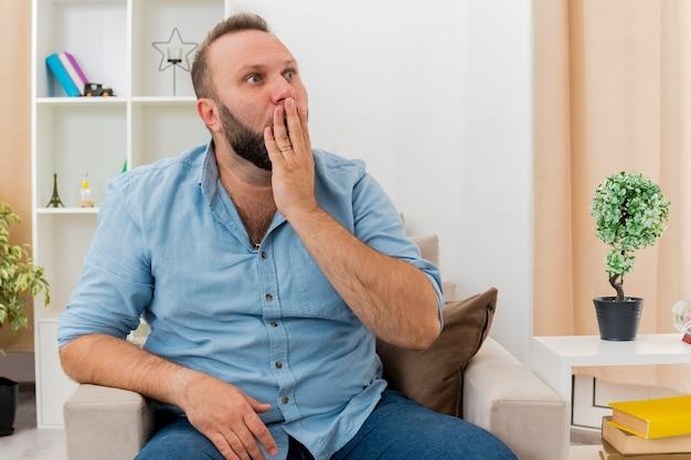 충격을받은 성인 슬라브어 남자는 거실 내부 측면을보고 입에 손을 넣어 안락 의자에 앉아