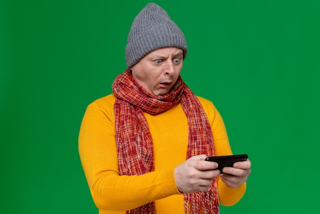 Shocked adult slavic man with winter hat and scarf around his neck holding and looking at phone