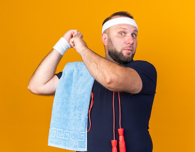 Shocked adult slavic sporty man with jumping rope around neck and with towel on shoulder wearing headband and wristbands pointing behind isolated on orange wall with copy space
