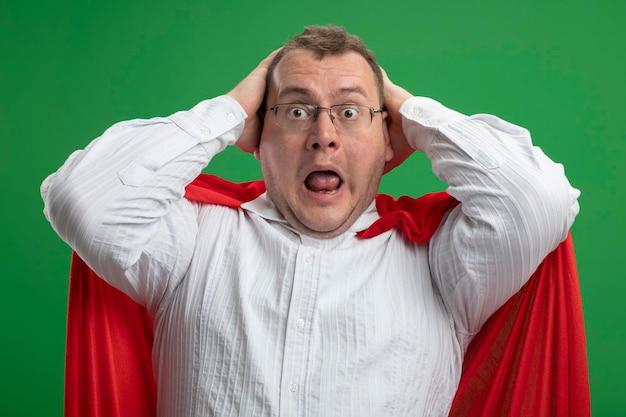 Uomo adulto scioccato del supereroe slavo in mantello rosso con gli occhiali che tiene la testa guardando la parte anteriore isolata sulla parete verde