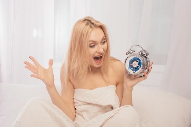 目覚まし時計を手にベッドでショックを受けた大人の女性