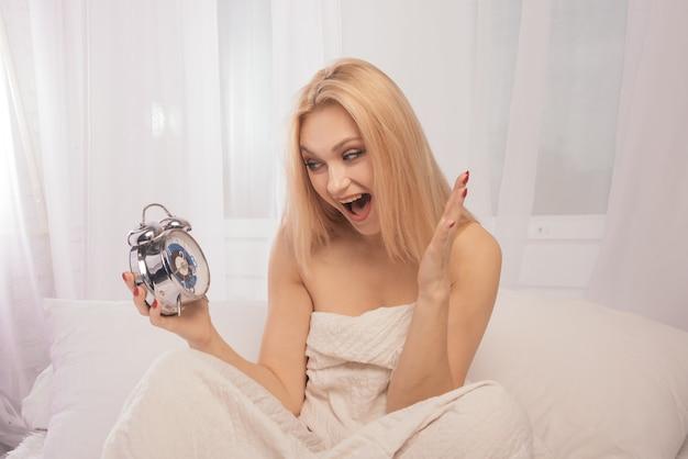 Шокированная взрослая женщина в постели с будильником