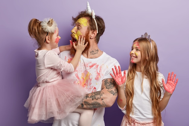 Shocked affectionate dad has dirty face from paints, opens mouth widely, holds little daughter on hands. smiling girl wears crown, shows palms in pink watercolors. joyful father and children have fun