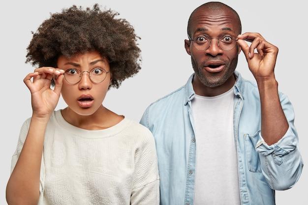 ショックを受けたアフリカ系アメリカ人の女性と男性の肌の色が濃く、眼鏡の縁に手を置いて、彼らに用意された驚きに驚いて、何かを信じることができず、白い壁に向かって屋内でポーズをとる