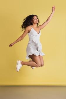 충격. copyspace와 노란색 벽에 고립 된 아프리카 계 미국인 아름 다운 여자의 초상화. 세련된 여성 모델. 인간의 감정, 표정, 판매, 광고, 패션, 청소년의 개념.